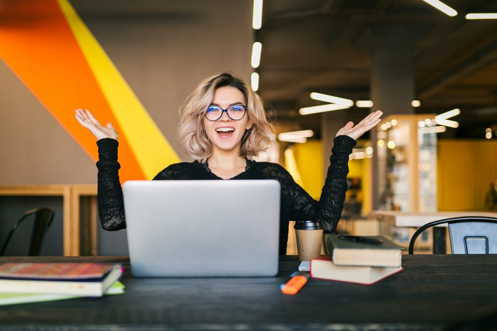 Young woman happy at her desk to learn