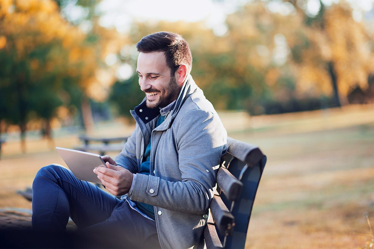 Man on a bench outside learning on tablet